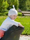 女婴坐一只石青蛙 图库摄影