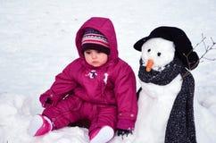 女婴坐室外在雪人旁边 免版税库存图片