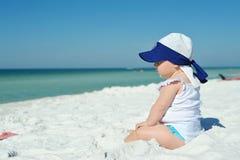 女婴坐看海洋的海滩 库存图片