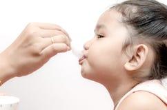 给女婴医学糖浆的母亲 免版税图库摄影