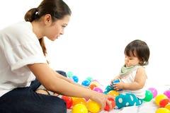 女婴打与她的母亲的球 免版税库存图片