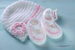 女婴托儿所桃红色和白色条纹羊毛赃物和帽子 免版税库存照片