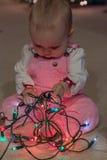 女婴探索圣诞灯串 免版税图库摄影