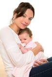 女婴放松了与在母亲胳膊的安慰者拥抱 库存照片