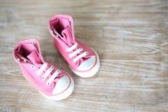 女婴的小的桃红色鞋子 免版税库存图片