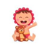 女婴笑的坐的拥抱玩具熊 皇族释放例证