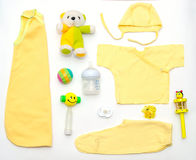 女婴黄色衣裳和玩具材料顶视图  免版税库存照片