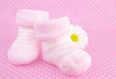 女婴被编织的桃红色鞋子袜子 免版税库存图片