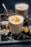 奶昔用巧克力、燕麦粥和芒果在玻璃 库存图片