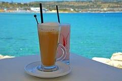 奶昔由新鲜的成熟草莓和冰冻咖啡制成在海背景 免版税库存图片