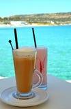 奶昔由新鲜的成熟草莓和被冰的咖啡制成在海背景 库存图片
