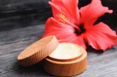 奶油和一朵桃红色花在木背景 库存图片