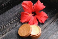 奶油和一朵桃红色花在木背景 免版税库存图片