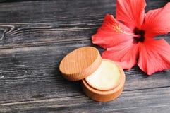 奶油和一朵桃红色花在木背景 库存照片