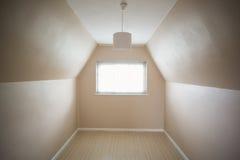 奶油和灰棕色的空的顶楼室 免版税库存图片
