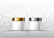 奶油的化妆瓶 白色瓶子和金子,在灰色背景的银色光滑的盒盖广告的 库存图片