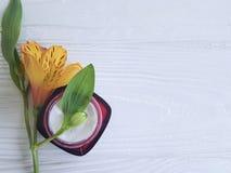 奶油色化妆用品,花在woodencleaner的成份德国锥脚形酒杯 免版税库存图片
