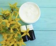 奶油色化妆自然容器黄色在蓝色木背景开花 库存图片