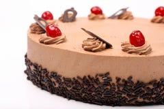 奶油色可可粉蛋糕用在白色背景的樱桃 库存照片