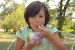 奶油色吃女孩冰木盆 免版税库存图片