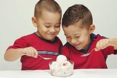 奶油色吃的冰孩子 免版税库存图片