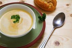 奶油色汤用荷兰芹在一块绿色板材,小圆面包的一个碗装饰 图库摄影