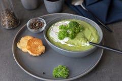 奶油色汤的关闭用硬花甘蓝和酸性稀奶油在灰色碗 免版税库存图片