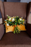 奶油色玫瑰和白色牡丹新娘花束在一个土气样式在棕色椅子 免版税库存图片