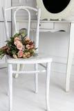 奶油色玫瑰美丽的精美花束在一把白色椅子放置在一个明亮的绝尘室,卧室 库存照片