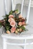 奶油色玫瑰美丽的精美花束在一把白色椅子放置在一个明亮的绝尘室,卧室 免版税库存照片