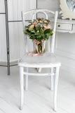 奶油色玫瑰美丽的精美花束在一把白色椅子放置在一个明亮的绝尘室,卧室 免版税库存图片