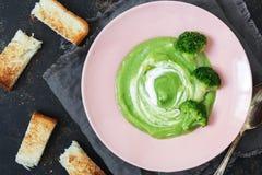 奶油色硬花甘蓝汤用在黑暗的背景的油煎方型小面包片 免版税库存图片