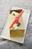 奶油色蛋糕用在白色板材的莓果在餐馆 库存照片