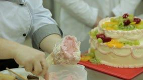 奶油色蛋糕用草莓、猕猴桃和黄色果冻调味料由厨师装饰 股票视频