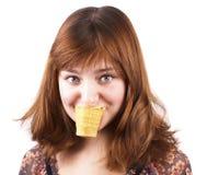 奶油色逗人喜爱吃滑稽的女孩冰纵向 免版税库存照片