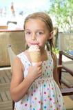 奶油色逗人喜爱的吃女孩冰少许 库存照片