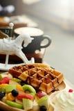 奶蛋烘饼倒巧克力汁和果子被混合的Served纯奶油并且喝与开胃菜的热的热奶咖啡 图库摄影