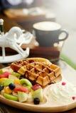 奶蛋烘饼倒巧克力汁和果子被混合的Served纯奶油并且喝与开胃菜的热的热奶咖啡 免版税库存图片