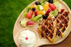 奶蛋烘饼倒巧克力汁和果子被混合的Served纯奶油并且喝与热的cappuchino 免版税库存照片