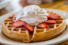 奶蛋烘饼冠上用草莓和打好的奶油 免版税库存照片
