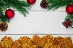 奶蛋烘饼和分支圣诞树和红色球与锥体在白色木葡萄酒背景 库存照片