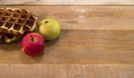 奶蛋烘饼和苹果在书桌上 免版税库存照片