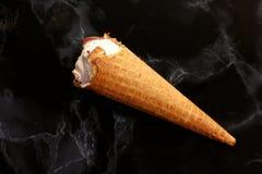 奶蛋烘饼在黑大理石背景的冰淇淋锥体 免版税图库摄影