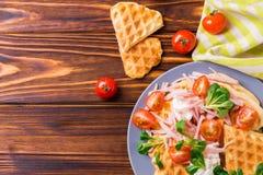 奶蛋烘饼将夹在中间用烟肉、西红柿和菜用结页草 免版税库存图片