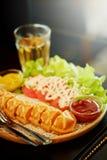 奶蛋烘饼热狗棍子设置了用沙拉和热的茶在桌上 免版税库存图片