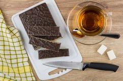奶蛋烘饼片断在切板、刀子和茶结块 免版税库存图片