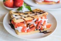 奶蛋烘饼用在木头的草莓 免版税库存图片