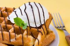奶蛋烘饼用巧克力汁、冰淇凌和薄菏在黄色背景 库存图片