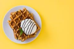 奶蛋烘饼用巧克力汁、冰淇凌和薄菏在黄色背景 免版税库存图片