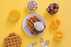 奶蛋烘饼用巧克力汁、冰淇凌和薄菏在黄色背景 库存照片